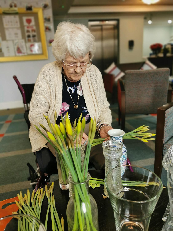Cedar View Resident arranging daffodils